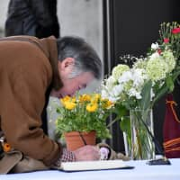 A man writes at the reception desk in front of the New Zealand Embassy in Tokyo on Tuesday to offer his condolences. | SATOKO KAWASAKI