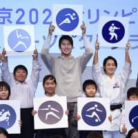 Shota Iizuka (center, back row), an Olympic medalist in the men's 4x100-meter relay, and Kiyo Shimizu of women's karate kata (center-right, back row) attend an event in Tokyo on Tuesday to announce the pictograms for the 2020 Tokyo Olympics. | KYODO
