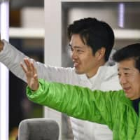 Former Osaka Mayor Hirofumi Yoshimura (left) and former Osaka Gov. Ichiro Matsui wave to voters Thursday in the city. The two recently resigned to call an election, running for the positions of governor and mayor respectively, to promote their plan to merge local governments. | KYODO
