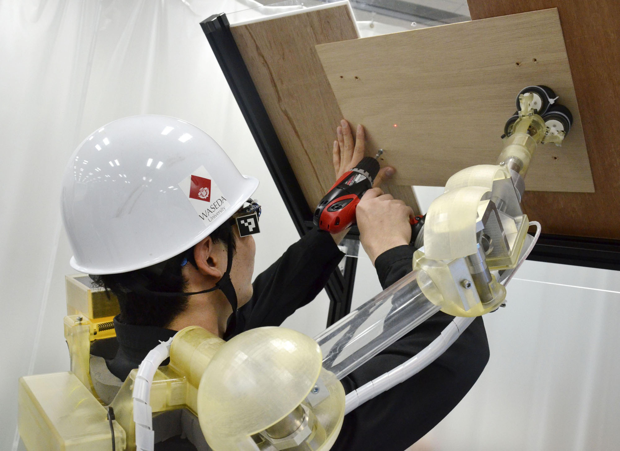 A wearable arm-shaped robot helps hold a board in place while a man drills into it during a demonstration in Tokyo in January. | KYODO