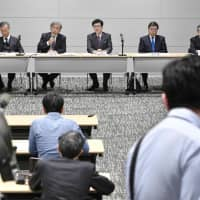 Executive board members of the Japan Society of Obstetrics and Gynecology hold a news conference Saturday in Tokyo's Chuo Ward after deciding to ease rules to allow qualified owners of private practices to conduct prenatal tests on pregnant women. | KYODO