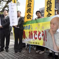 Lawyers hold banners Thursday after the Kumamoto District Court acquitted their client, Koki Miyata, of murder more than 30 years after he was found guilty of killing his shogi partner Matao Okamura in 1985. | KYODO