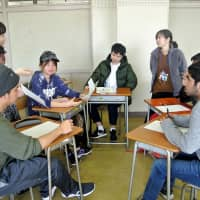 Mariko Saya (standing, right), a multicultural education coordinator and Japanese-language teacher, talks with foreign students during a class at Sagami Koyokan High School in Zama, Kanagawa Prefecture. | KYODO