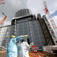 Two people wearing protective suits and masks talk in front of the No. 3 reactor building at the tsunami-crippled Fukushima No. 1 nuclear power plant in Okuma, Fukushima Prefecture, on Feb. 18. | REUTERS