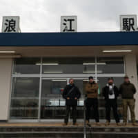 Emil Truszkowski and three friends stand in front of Namie Station in Fukushima Prefecture, during a tour provided by nonprofit organization Nomado in January. | COURTESY OF EMIL TRUSZKOWSKI