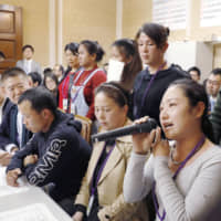A group of foreign technical interns speak about abusive working conditions forced on them by employers during a news conference at the Diet in November. | KYODO