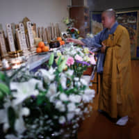 Thich Tam Tri offers incense sticks earlier this month in front of an altar at Nisshinkutsu Temple in Minato Ward, Tokyo. Along the wall are wooden mortuary tablets inscribed with the names of Vietnamese students or workers who died after coming to work or study in Japan. | REUTERS