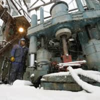 A man inspects machinery that is being used to conduct a geothermal survey in the city of Yuzawa, Akita Prefecture. | KYODO