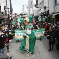 A man dressed as the patron saint of Ireland leads a St. Patrick's Day parade in Yokohama's Motomachi district in 2018. | COURTESY OF HIDEKI MIMURA