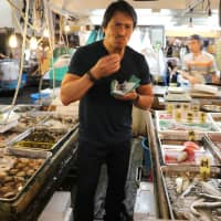 Developing a taste for seafood: Tetsuya 'Nick' Sakagami tries some the fare at Tokyo's Tsukiji fish market in 2018, before it closed and moved to Toyosu.  'Sushi Master' (Quarry Books, 2019)