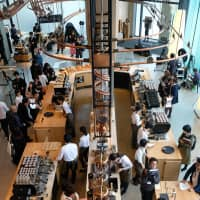 A hub of activity: Baristas pour coffee and offer drink consultations at the Starbucks Reserve Roastery Tokyo's first-floor main bar.   CLAIRE WILLIAMSON