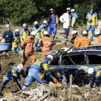 Rescue personnel conduct a search for missing people on July 9 in the town of Kumano, Hiroshima Prefecture, hit by landslides triggered by torrential rain. | KYODO