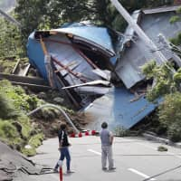 A house lies in ruins across a road in the town of Atsuma, where 36 residents were killed by landslides caused by a magnitude 6.7 quake that hit Hokkaido on Sept. 6. | KYODO