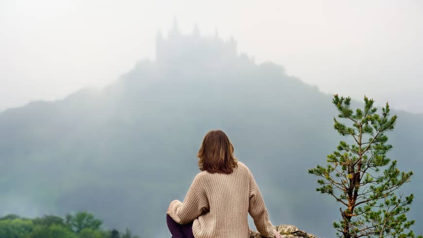 Looking good: A tourist stares at Germany's Hohenzollern Castle, which looks peaceful in the distance. The landmark is one of many overseas that employ strict rules to make sure everyone who visits has an enjoyable experience.