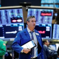 Traders work on the floor of the New York Stock Exchange on Tuesday. | REUTERS