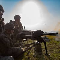 U.S. Marines fire an automatic grenade launcher at Camp Hansen in Okinawa Prefecture on Jan. 30. | 3RD MARINE LOGISTICS GROUP