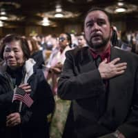 Newly naturalized U.S. citizens recite the Pledge of Allegiance during a naturalization ceremony in Oakland, California, on Feb. 13. | BLOOMBERG