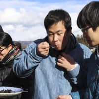 Students try zazamushi tsukudani, a dish of insect larvae simmered in soy sauce, mirin (rice wine), sugar and sake. | KYODO