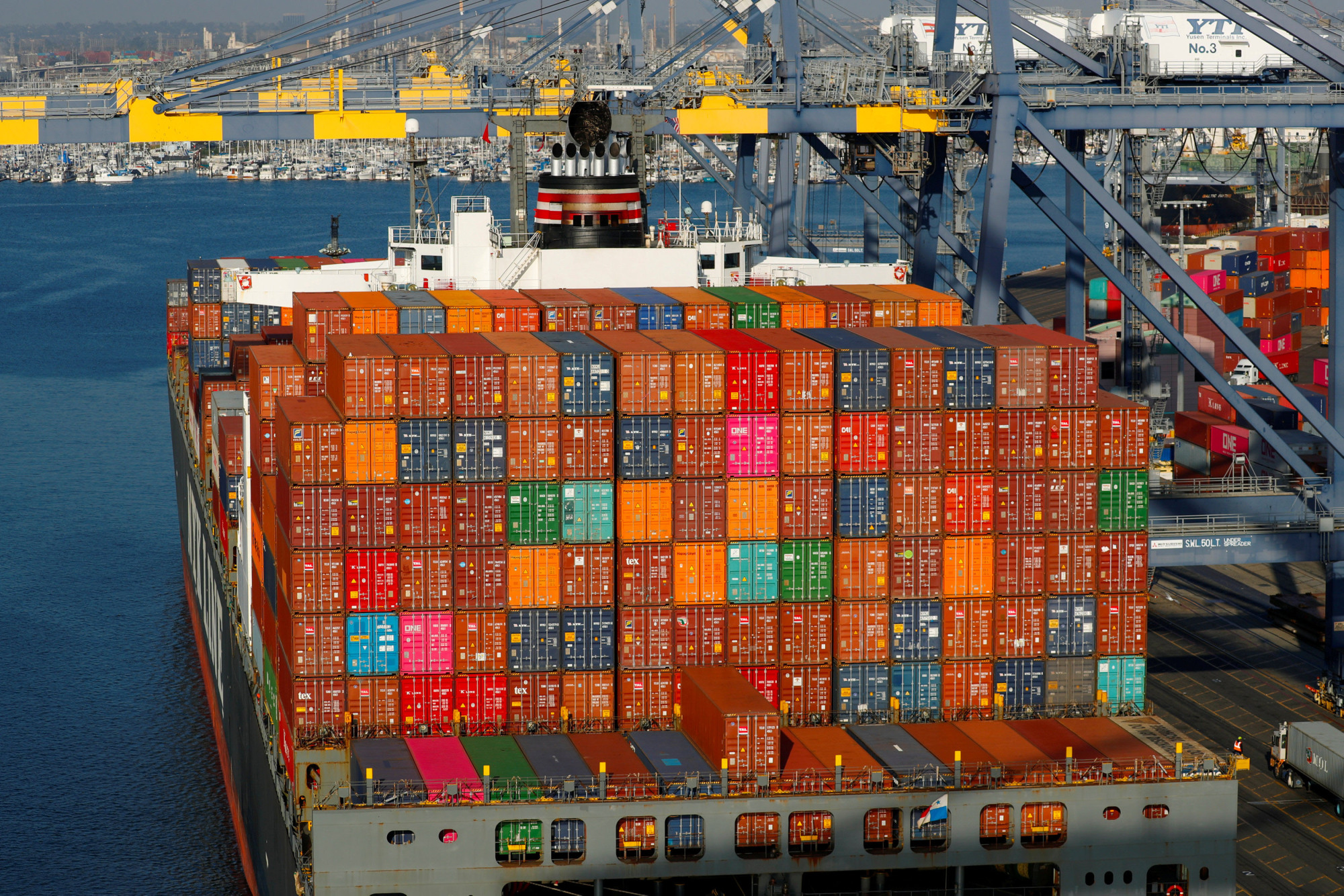 Shipping containers are seen stacked on ships at the Port of Los Angeles on Jan. 30. The U.S. trade deficit has soared since 2016. | REUTERS