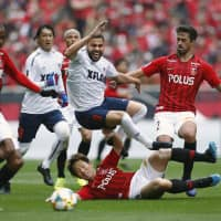 Urawa's Diego Oliveira (left) moves for the ball against FC Tokyo at Saitama Stadium on Saturday afternoon. | KYODO