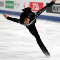 Nathan Chen competes to 'Land of All' in the men's free skate at the World Figure Skating Championships on Saturday night at Saitama Super Arena. Chen retained his title with 323.42 points. | REUTERS