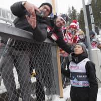 Ryoyu Kobayashi poses with fans for a photo after the FIS Ski Jumping World Cup men's team competition in Holmenkollen, Oslo, on Saturday. | AP