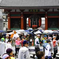 Some of the runners participating in Sunday's Tokyo Marathon take photographs as they pass by Sensoji Temple in the capital's Asakusa district. | YOSHIAKI MIURA