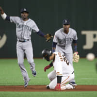 Seattle second baseman Dee Gordon (left) throws to complete a double play as Yomiuri's Kazuma Okamoto is forced out at second. | AP