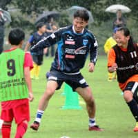 Kazuyoshi Miura chases a ball with elementary school children at a soccer clinic in Fukushima in September 2012. | KYODO