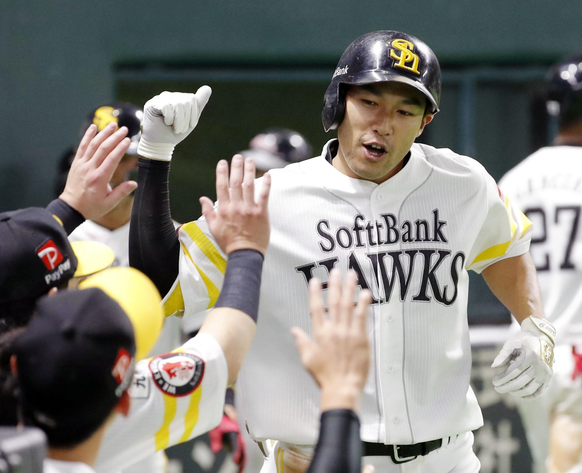 Hawks slugger Yuki Yanagita is greeted by teammates after hitting a two-run home run against the Lions on Sunday at Yafuoku Dome.   KYODO