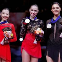 Runner-up Elizabet Tursynbaeva of Kazakhstan (left), gold medalist Alina Zagitova of Russia and third-place finisher Evgenia Medvedeva of Russia pose for photographers on the awards podium after the completion of the women's free skate on Friday. | REUTERS