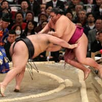 Ozeki Takayasu (left) pushes out komusubi Mitakeumi out of the ring on Monday at Edion Arena Osaka on the second day of the Spring Basho. | NIKKAN SPORTS