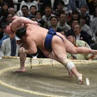 Yokozuna Hakuho (left) unleashes a throw to beat No. 4 maegashira Tochiozan and stay undefeated on Sunday, the eighth day of the Spring Grand Sumo Tournament in Osaka. | NIKKAN SPORTS