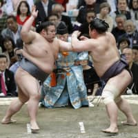 Sekiwake Takakeisho (left) utilizes a tsuki-oshi (pushing-thrusting) attack to beat No. 2 maegashira Myogiryu on the opening day of the Spring Basho on Sunday in Osaka. | KYODO