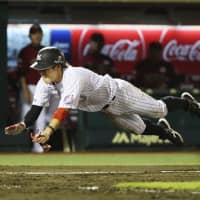 The Marines' Daichi Suzuki dives into home plate during the ninth inning of a game against the Eagles on Aug. 19, 2018, in Sendai. | KYODO