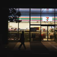 A pedestrian walks past a 7-Eleven convenience store, operated by Seven & I Holdings Co., at night in Kawasaki in April 2016. | BLOOMBERG