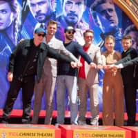 Left to right: Marvel Studios Persident Kevin Feige, actors Chris Hemsworth, Chris Evans, Robert Downey Jr., Scarlett Johansson, Mark Ruffalo and Jeremy Renner of 'Avengers: Endgame,' place their hand prints in cement at TCL Chinese Theatre IMAX Forecourt on Tuesday in Hollywood, California. | AFP-JIJI