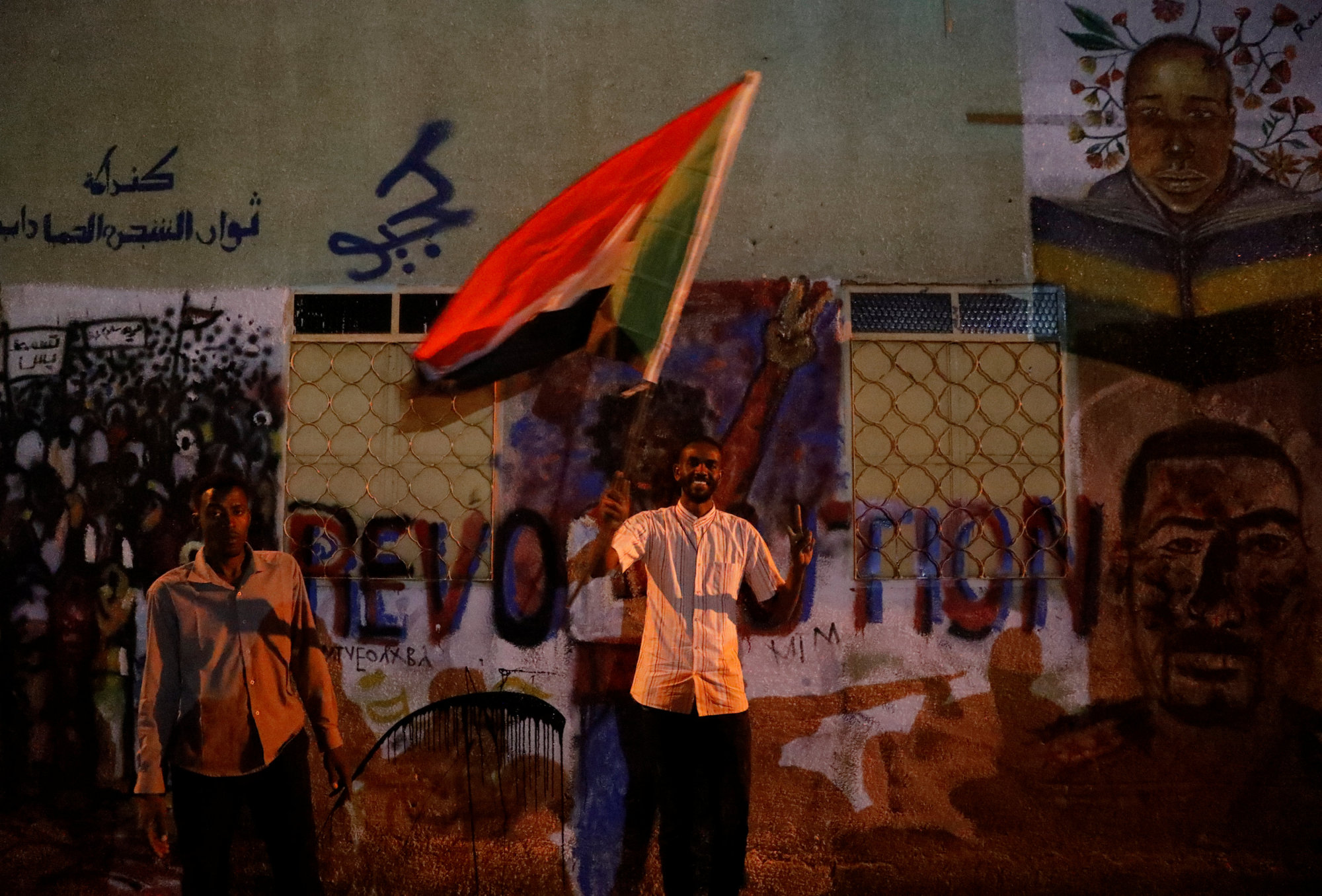 A Sudanese protester waves a national flag as he arrives a mass protest in front of the Defense Ministry in Khartoum on Sunday. | REUTERS