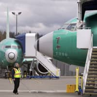 A worker looks up at a parked Boeing 737 Max 8 built for Jet Airways as another 737 Max 8 made for Shenzhen Airlines stands behind at a Boeing Co. production facility in Renton, Washington, Monday. Orders and deliveries of Boeing's 737 Max plunged in the first quarter as the plane was grounded around the world following a second deadly crash. Boeing disclosed Tuesday that it received no new orders for the Max in March. | AP