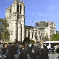 People gather in front of Notre-Dame Cathedral in Paris on Wednesday, two days after a big fire gutted part of the iconic building, a designated UNESCO World Heritage site. | KYODO
