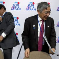 Finance Minister Taro Aso and Bank of Japan Gov. Haruhiko Kuroda leave a Group of 20 news conference during the World Bank/IMF Spring Meetings in Washington on Friday. | AP