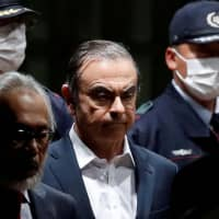 Former Nissan Motor Co. Chairman Carlos Ghosn leaves the Tokyo Detention House with his lawyer after being released on bail Thursday. | REUTERS