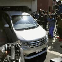 A Tokyo Prosecutor's Office vehicle, believed to be carrying former Nissan Chairman Carlos Ghosn, leaves his residence in Tokyo on Thursday morning. | KYODO