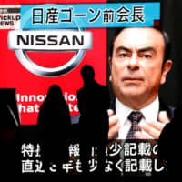 Passersby are silhouetted as a huge street monitor broadcasts news reporting ousted Nissan Motor chief's Carlos Ghosn's indictment and re-arrest in Tokyo in December. | REUTERS