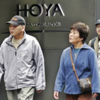 Pedestrians walk past in front of Hoya Corp. headquarters in Tokyo. The leading Japanese eyeglass lens maker was hit by a cyberattack at its key production base in Thailand in late February.   BLOOMBERG NEWS