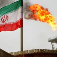 A gas flare from a production platform in the Soroush oil fields in the Persian Gulf is seen alongside an Iranian flag. | REUTERS / VIA KYODO