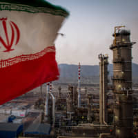 An Iranian national flag flies at the Persian Gulf Star Co. gas condensate refinery in Bandar Abbas, Iran, in January.   BLOOMBERG