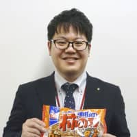 A Kameda Seika Co. employee holds a bag of crispy rice crackers with roasted peanuts, known as Kaki No Tane in Japan and Kameda Crisps abroad. | KYODO