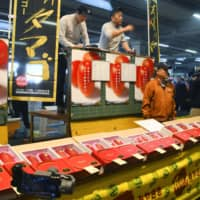 Premium mangoes called Taiyo no Tamago are auctioned at a wholesale market in Miyazaki Prefecture on Monday. | KYODO