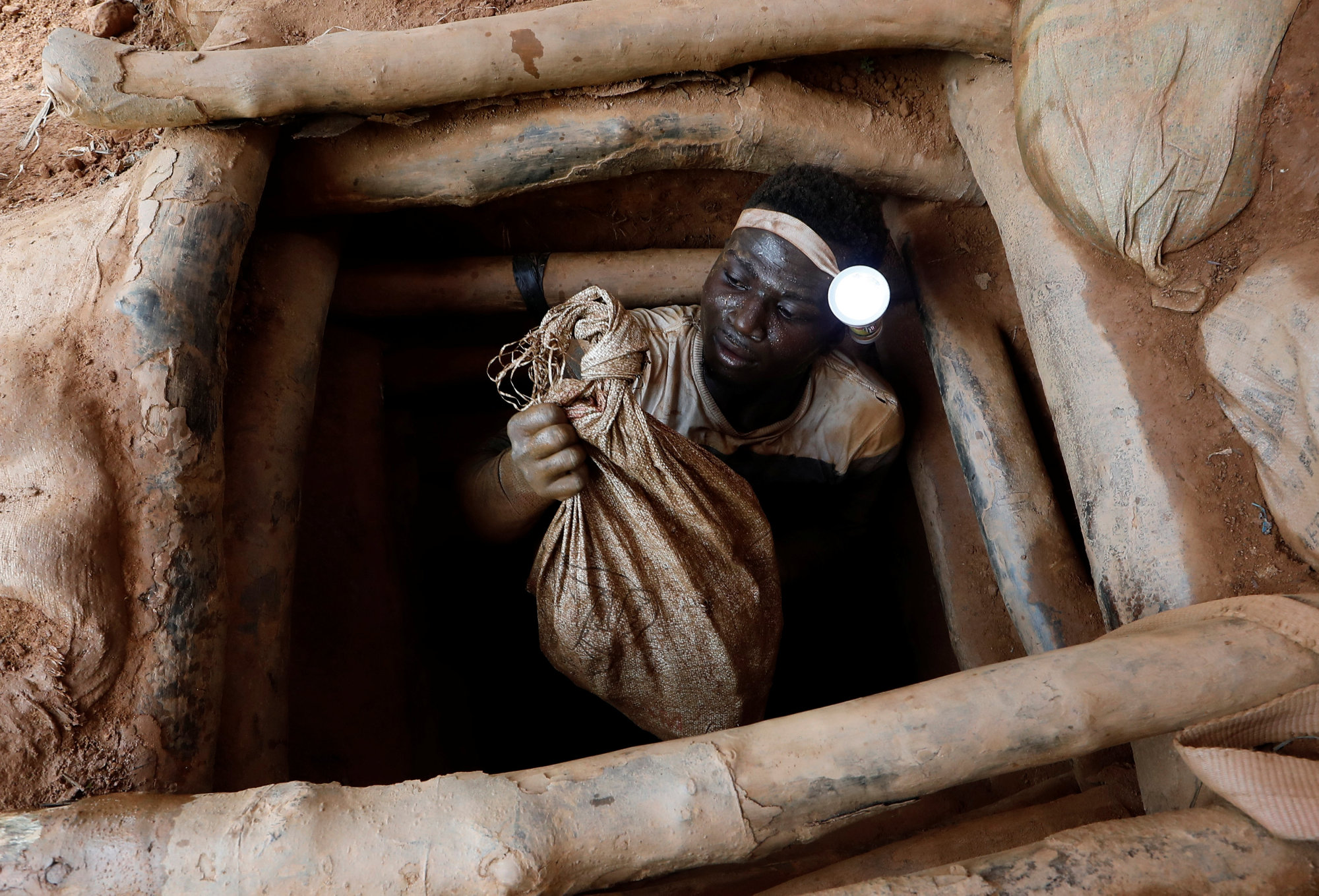 An artisanal miner climbs out of a gold mine with a bag of rocks broken off from inside the mining pit at the unlicensed mining site of Nsuaem Top in Ghana in November. | REUTERS